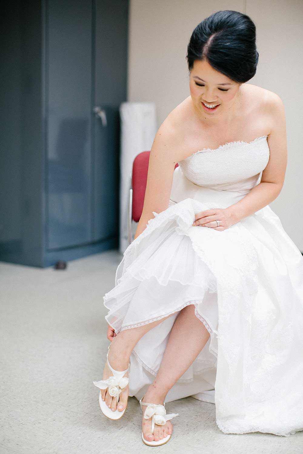 The Bride Putting On Her Shoes In A White Strapless Satin Wedding