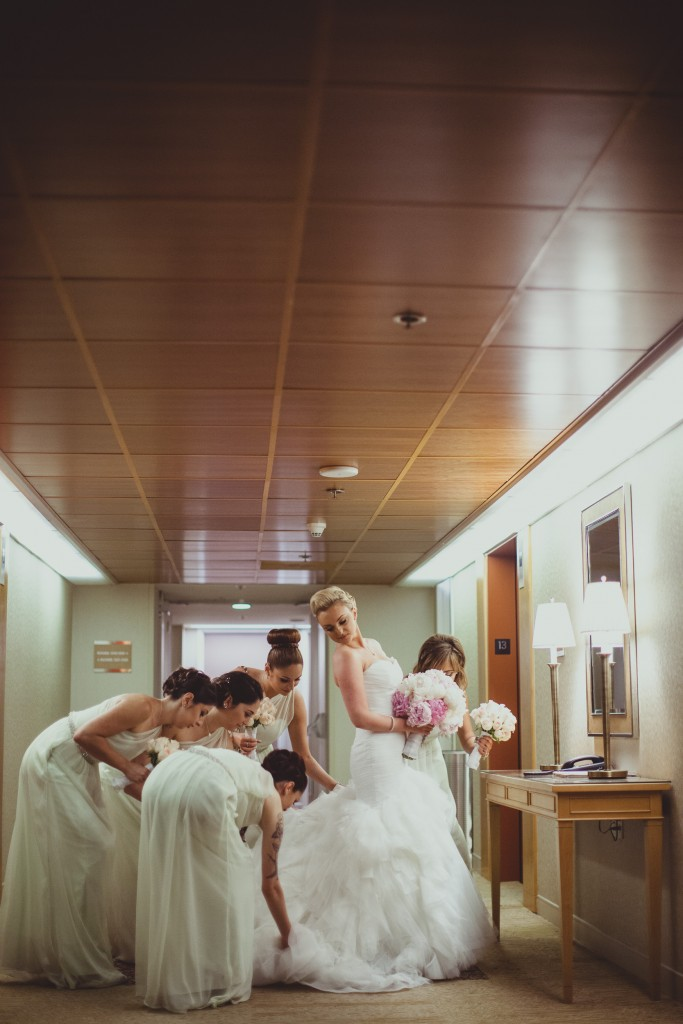 Bridesmaids helping with the brides dress