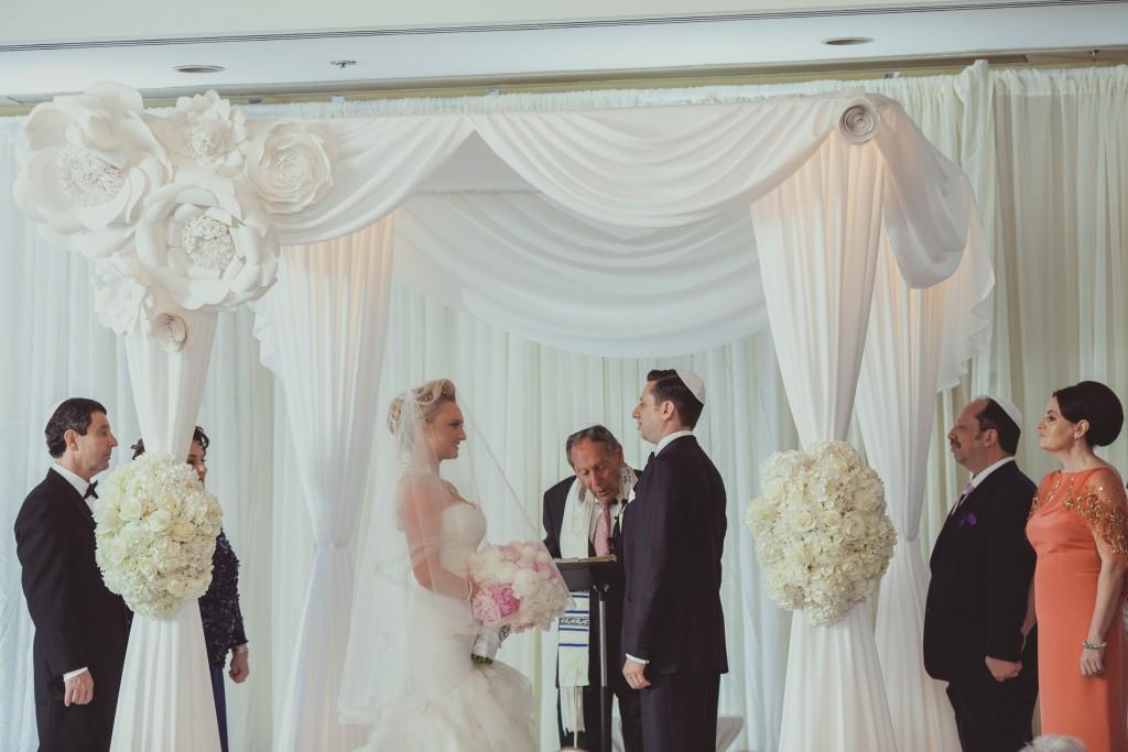 Wedding ceremony under white drapped altar