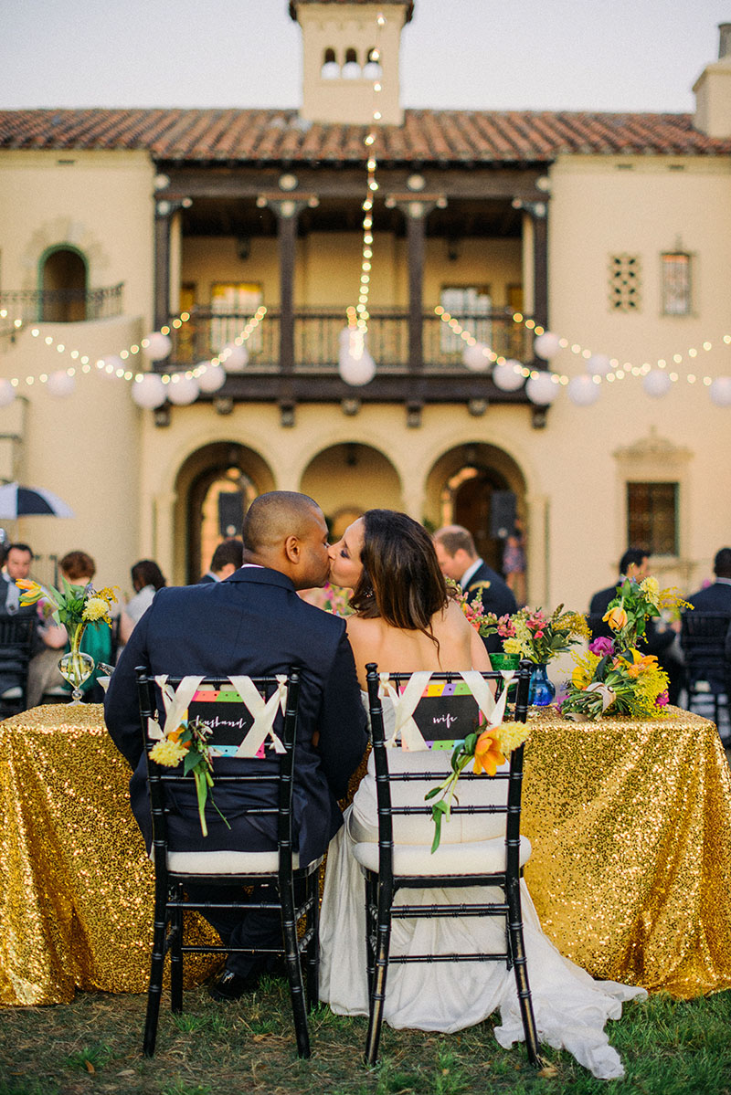 Bride and Groom at Gold Sequin Clothed Sweetheart's Table
