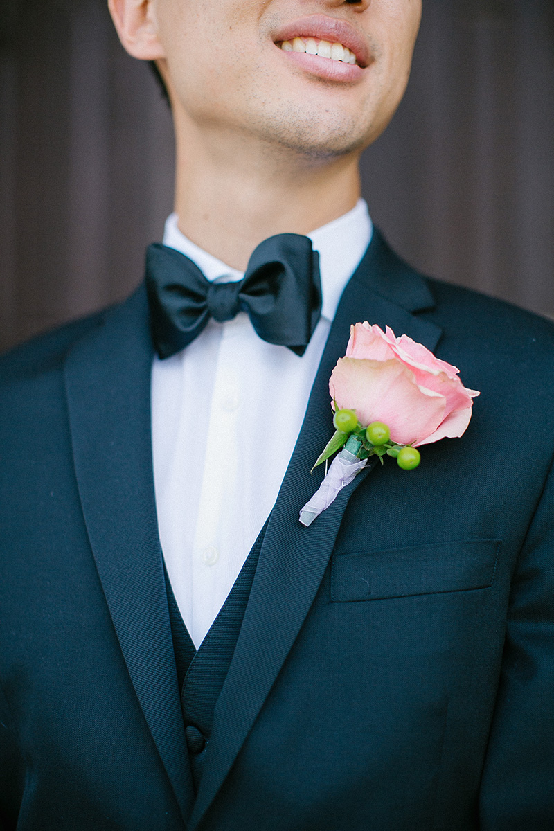 A navy blue tux with a pink rose boutonierre
