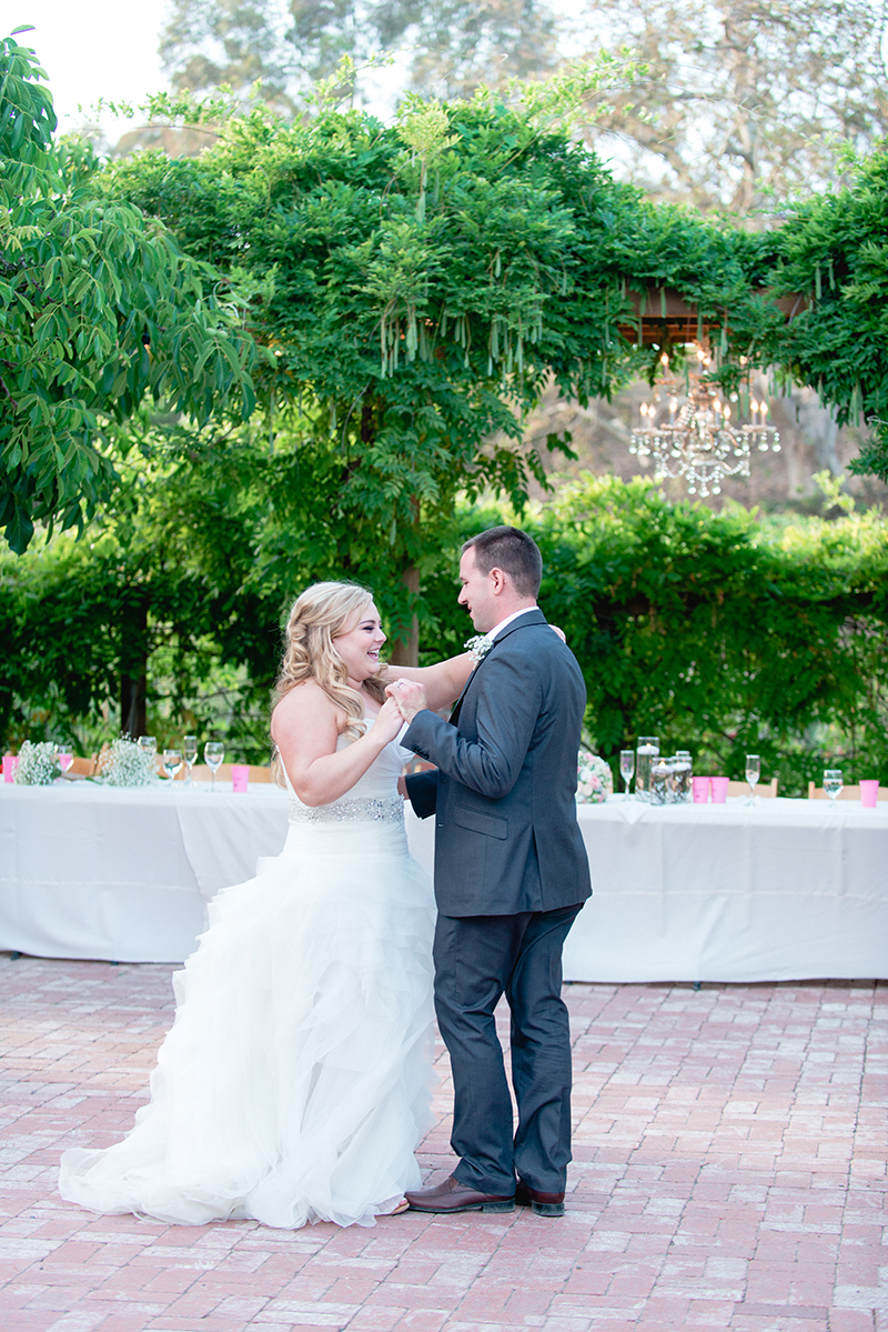 bride and groom's first dance with greenery background