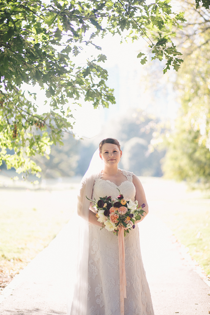 Bride in Lace Gown with Peach and Plum Floral Bouquet
