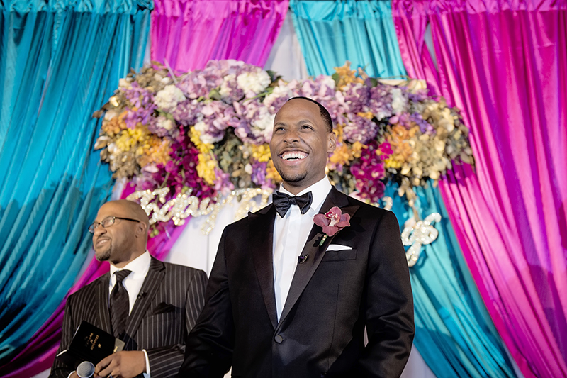Excited Groom Waiting for his Bride at Vibrant Indoor Wedding Ceremony