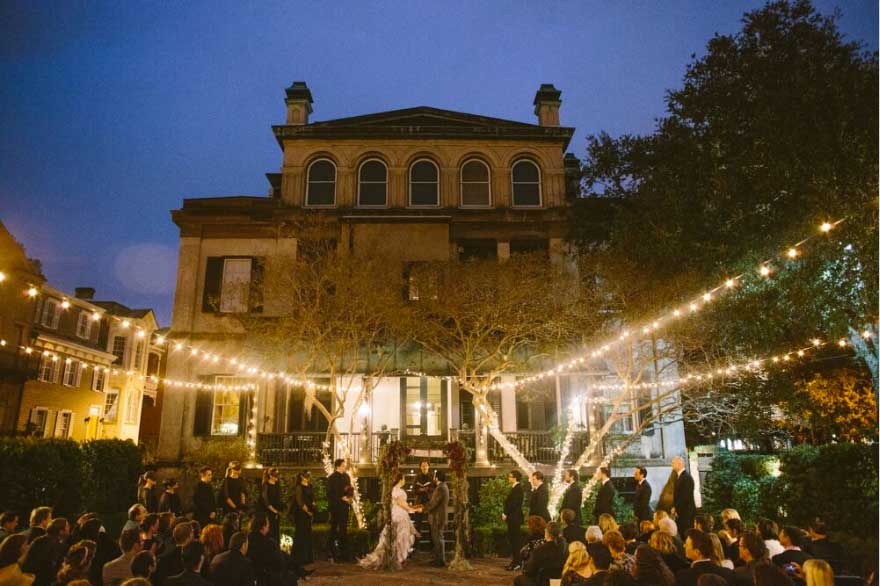 Intimate outdoor wedding ceremony under string lights at night