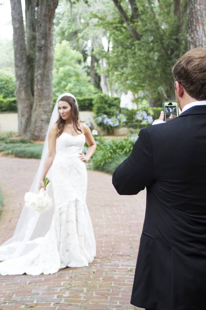 Groom Taking a Picture of His Bride