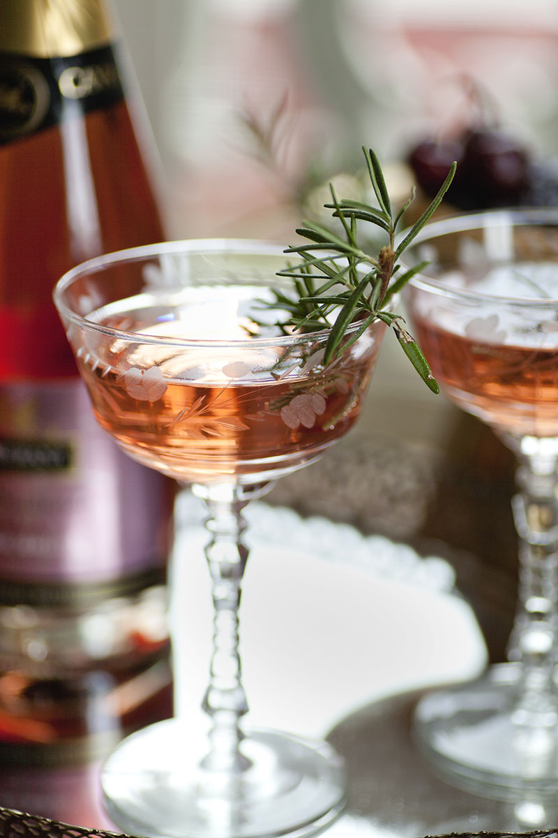 Red Signature Cocktail with Rosemary Garnish