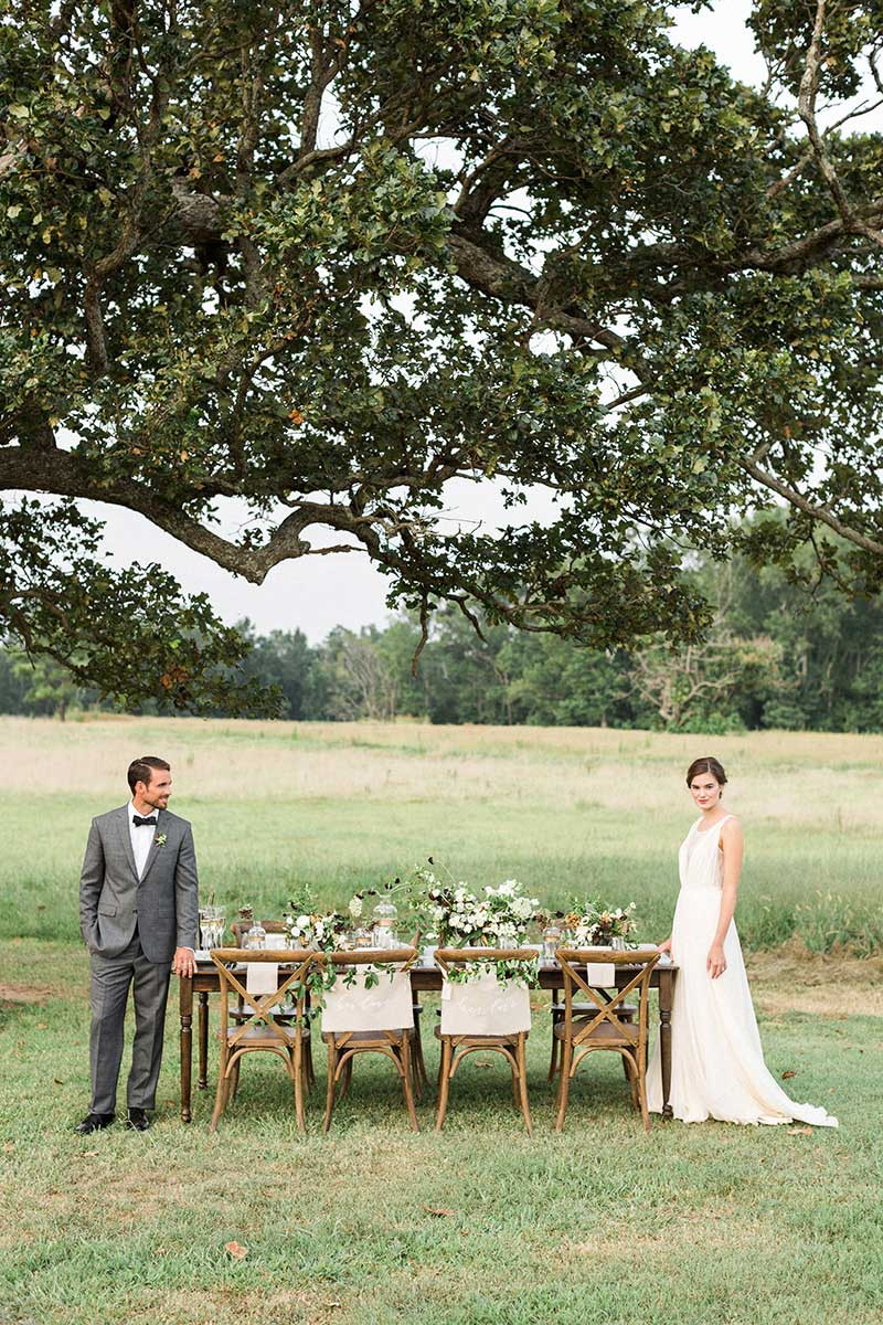 Rustic-Outdoor-Wedding-Reception-Table-Setting-with-Bride-and-Groom