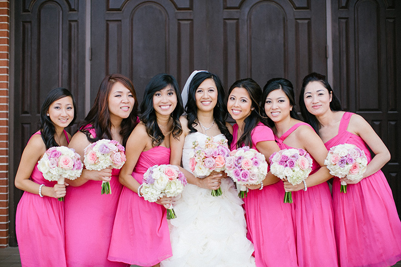 The bride with the bridesmiads in short hot pink dresses