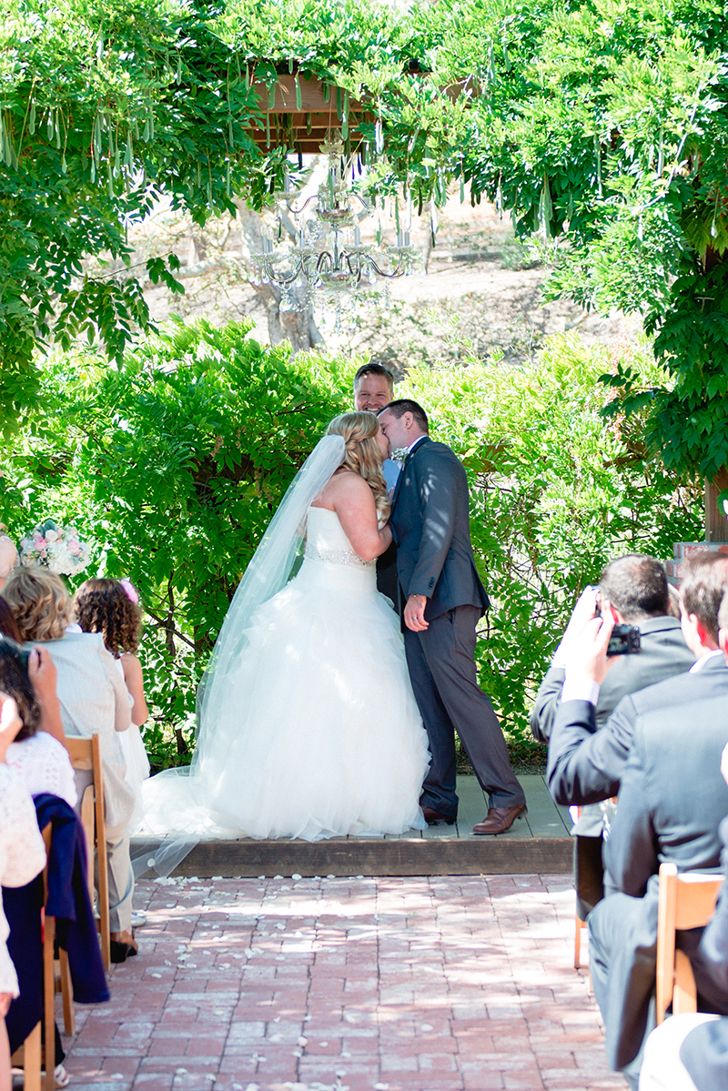 bridge and grooms first kiss under greenery altar