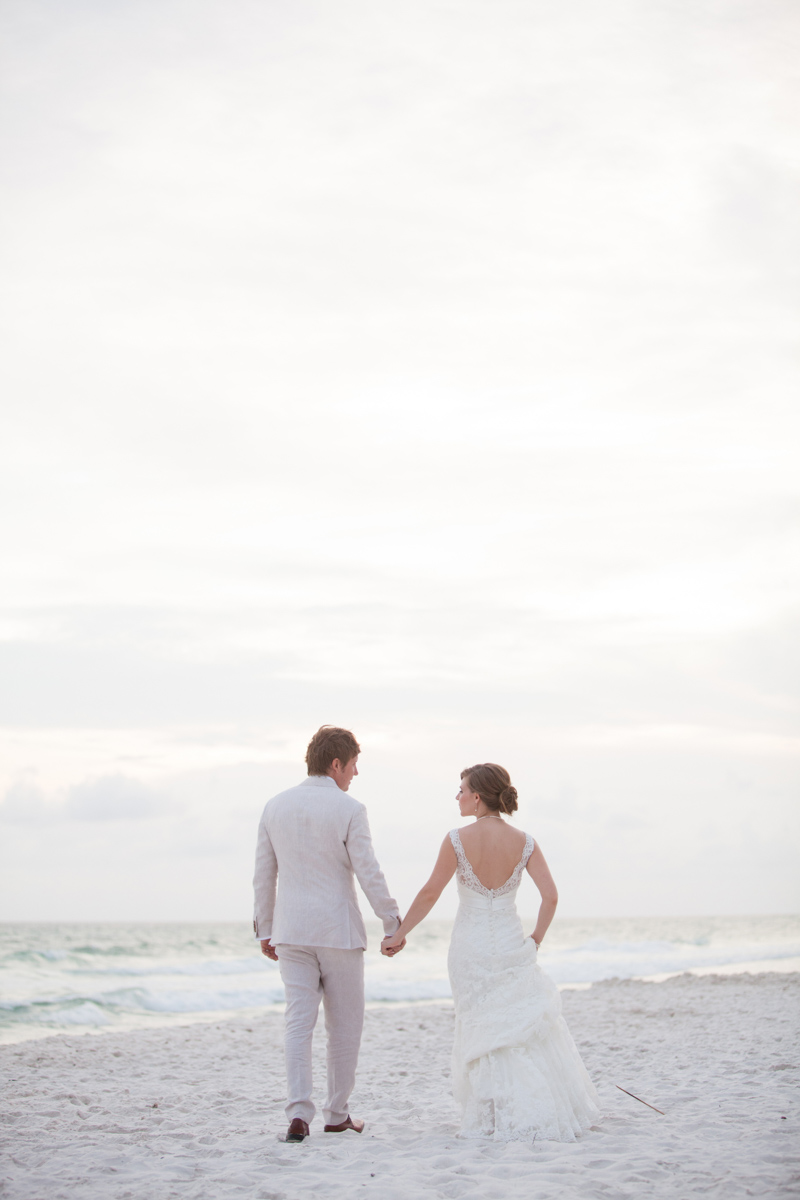 Backshot of bride and groom holding hands on white sand beaches