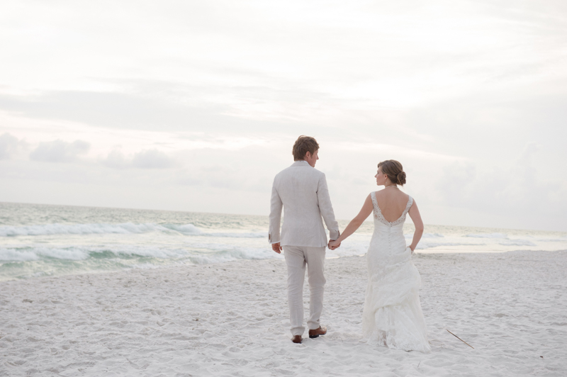 Backshot of bride and groom walking on the beach