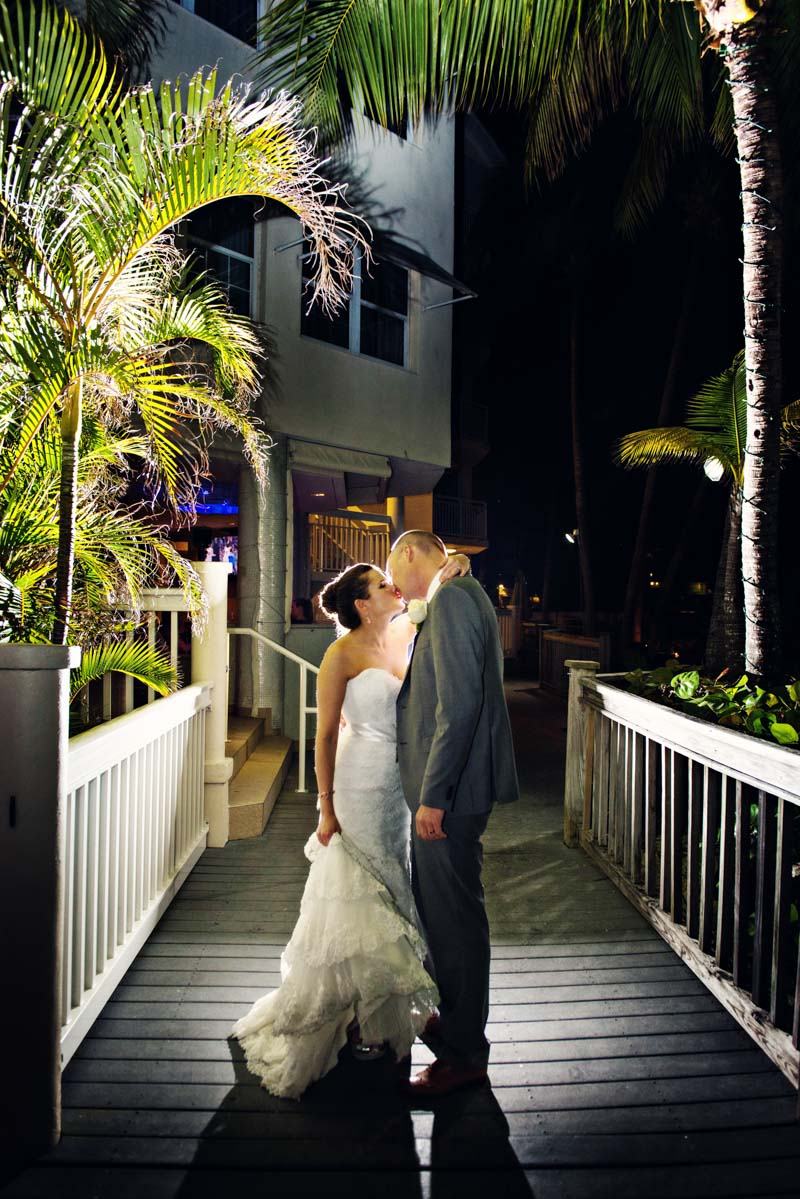Bride and groom kissing night shot on dock