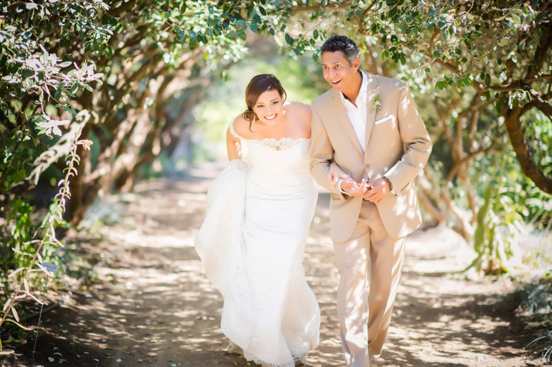 Bride and groom walking through overlapping branches