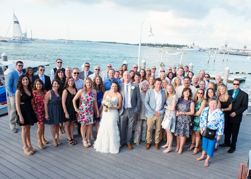 Bride and groom with wedding guest group shot overlooking the water