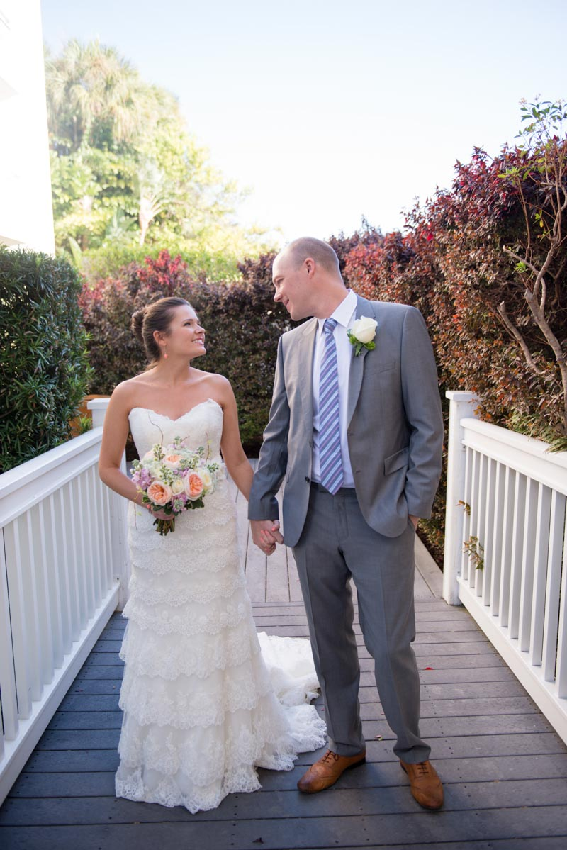 Bride holding pink garden rose bouquet and grooms hand