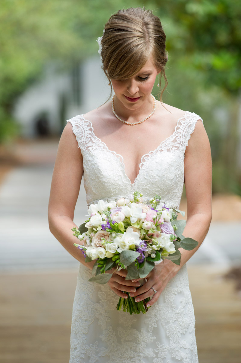 Bride in lace dress holding purple and cream bouquet