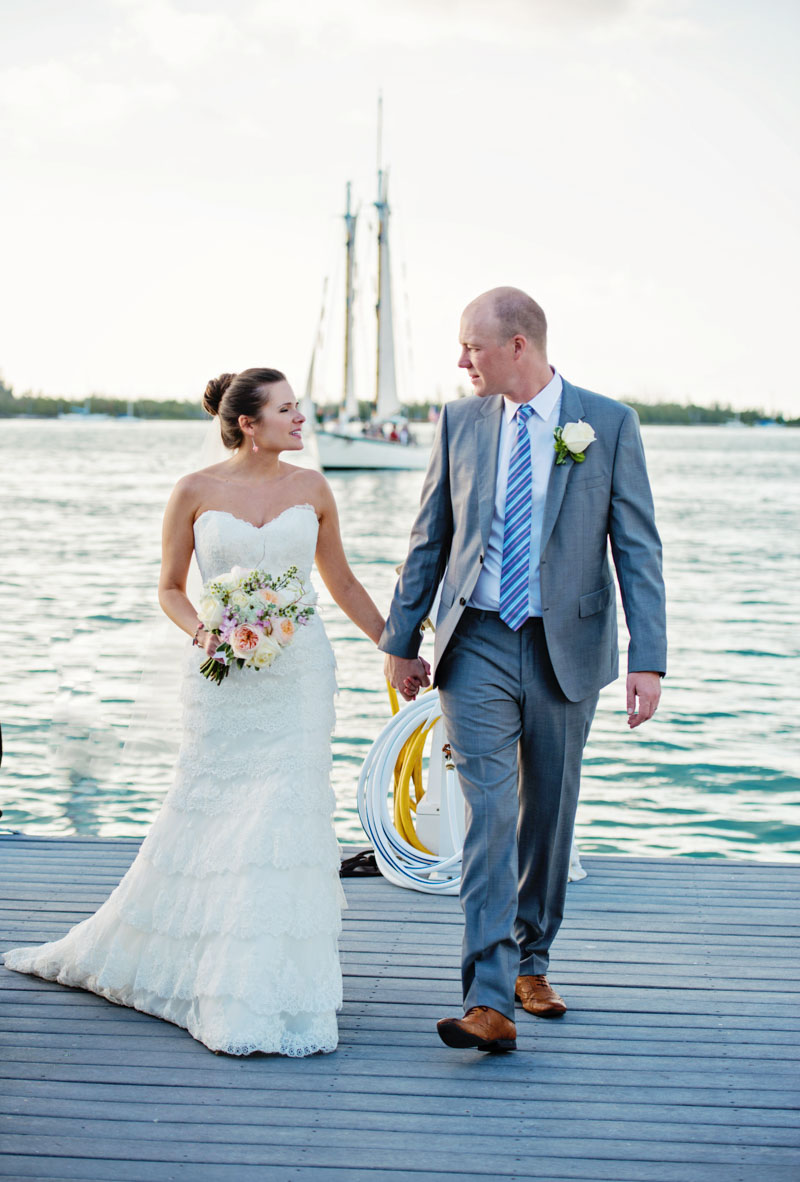 Bride in layered ivory lace gown walking with groom