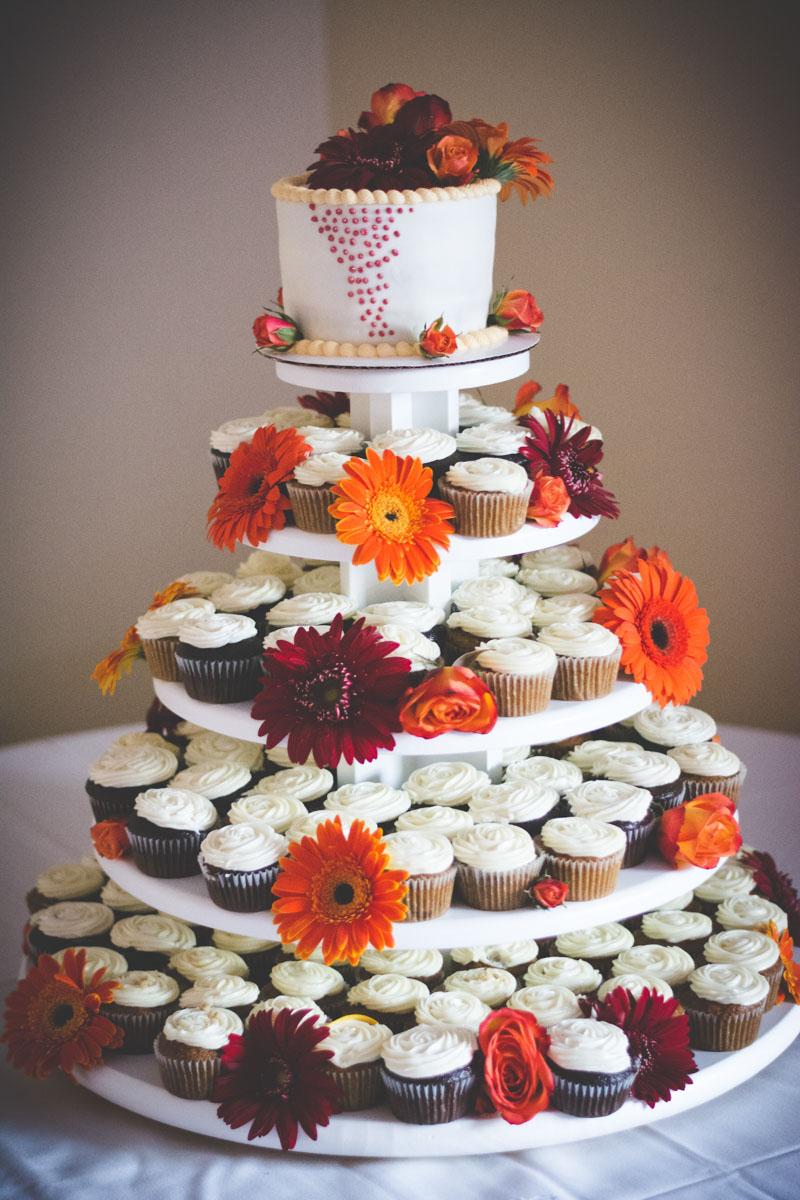 Chocolate and vanilla cupcake wedding cake detailed with garnet and orange gerbera dasies