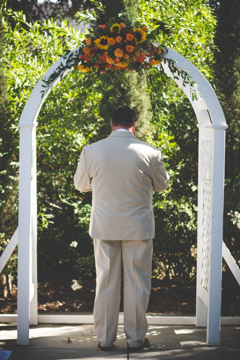 Groom in khaki waiting under white wooded altar