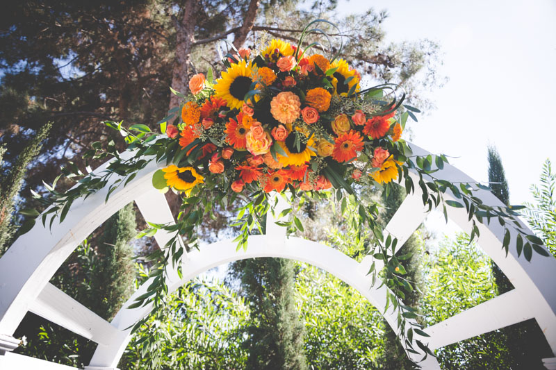 Yellow sunflowers orange carnations and roses topping white wooden altar
