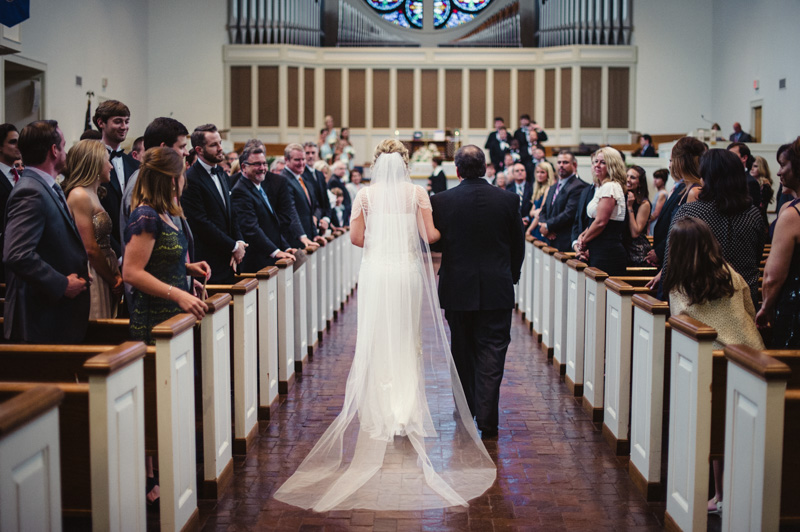 Backshot of bride walking down the isle with chiffon white veil