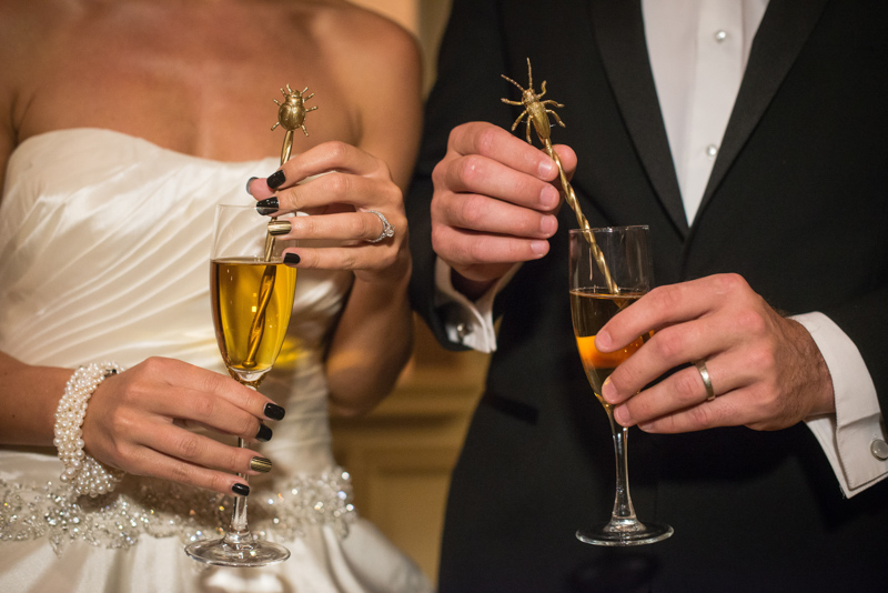 Bride and groom holding gold assorted bug drink stirrers