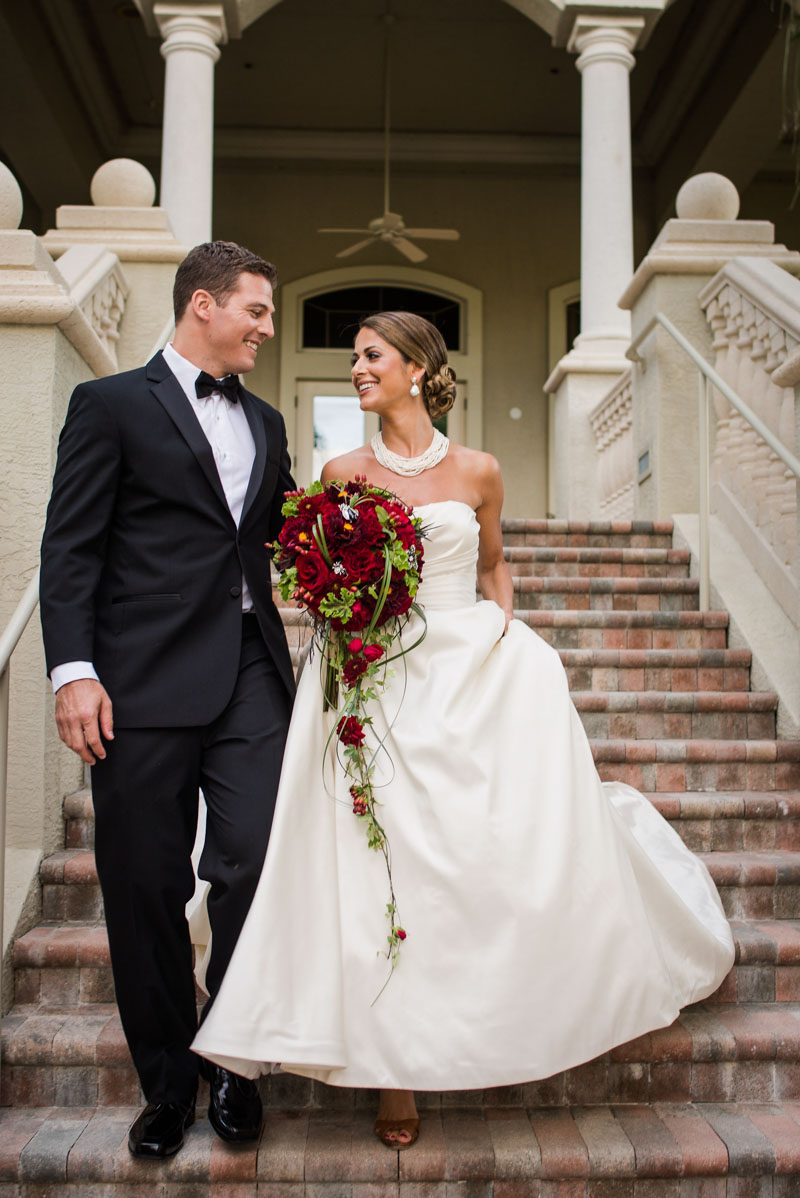 Bride in strapless cream gown holding red rose ball bouquet