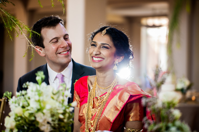 Bride in traditional Indian attire smiling with groom