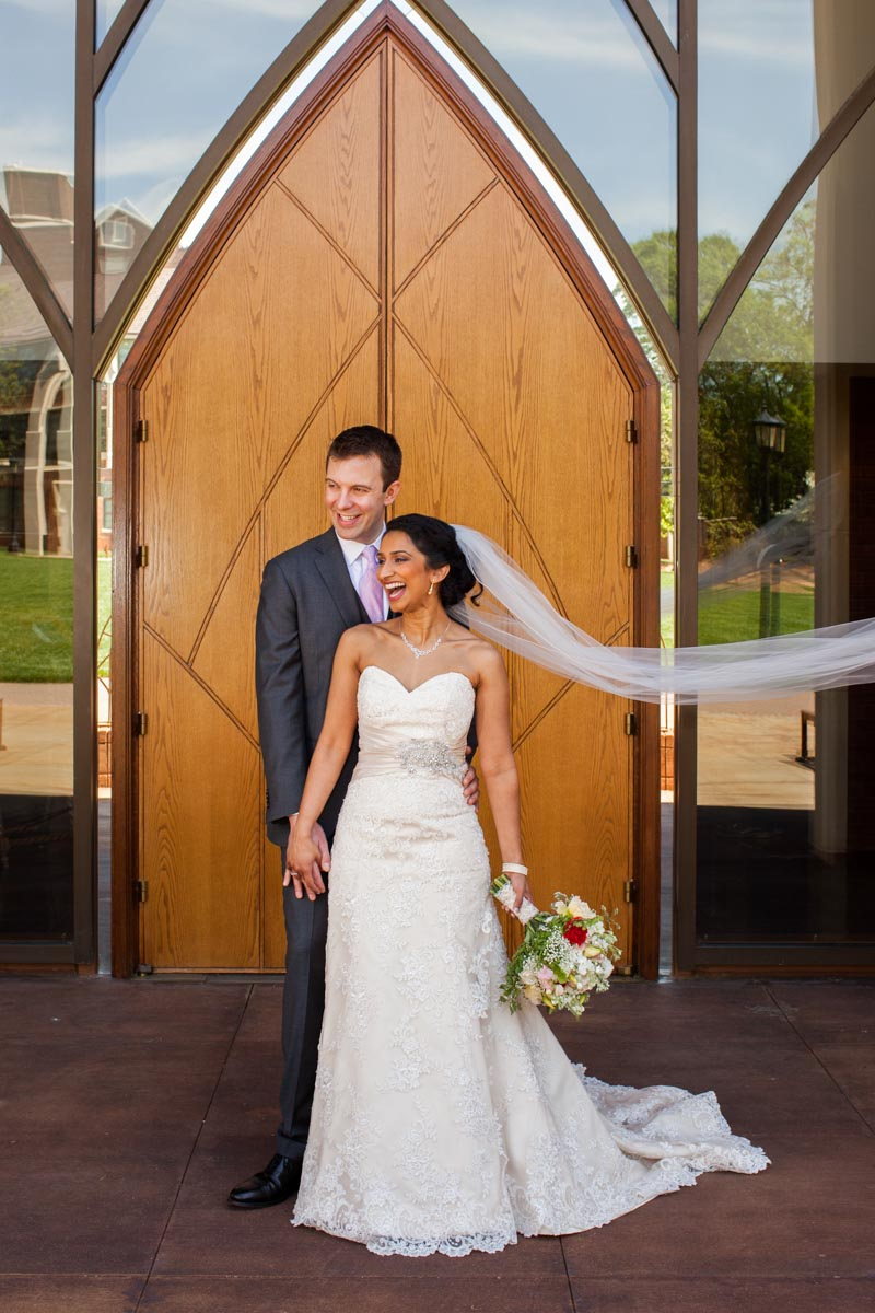 Bride with white tulle veil outside of church with groom
