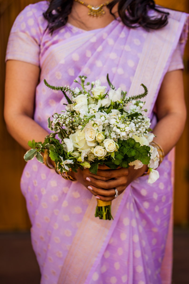 Bridesmaid in traditional purple Indian attire holding baby's breath bouquet