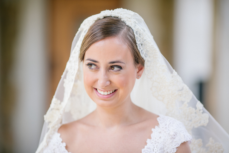Candid of bride in lace veil smiling