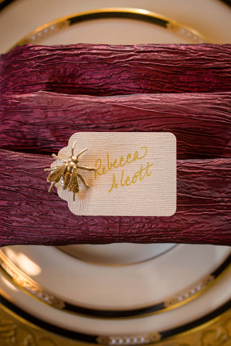 Escort card in gold font with a gold bug accesory
