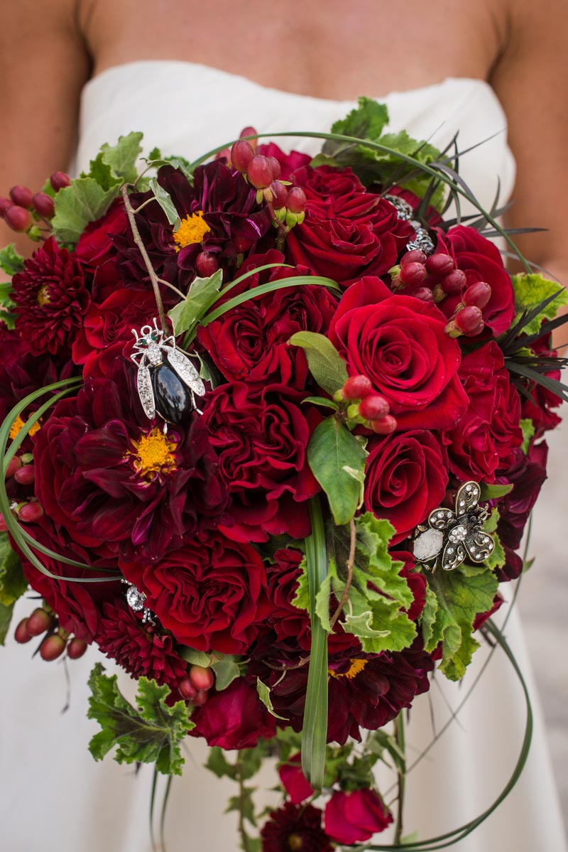 Mixed red rose circle bouquet with assorted bug brooches mixed in