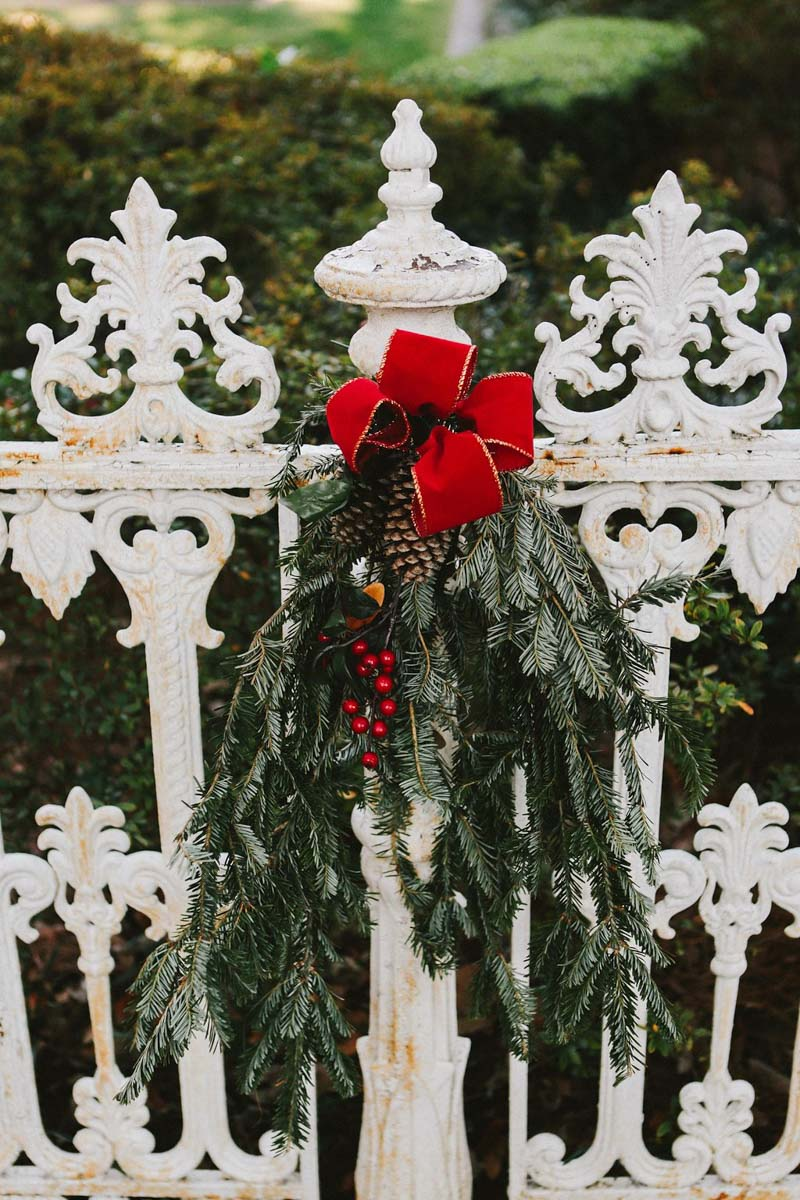 Wedding Reception White Fence with Holiday Decoration Evergreen, Pine Cone, and Red Bow