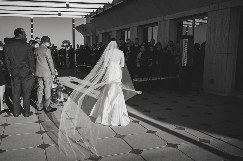 B&W shot of bride walking down the aisle with chiffon veil
