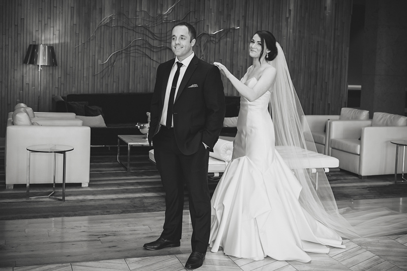 B&W shot of first look with bride tapping the grooms shoulder