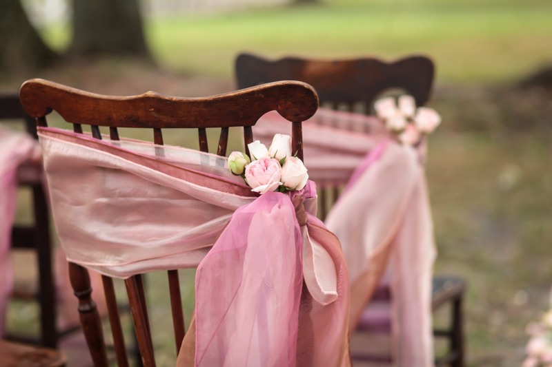 Blush fabric tied to a vintage chair for the ceremony_