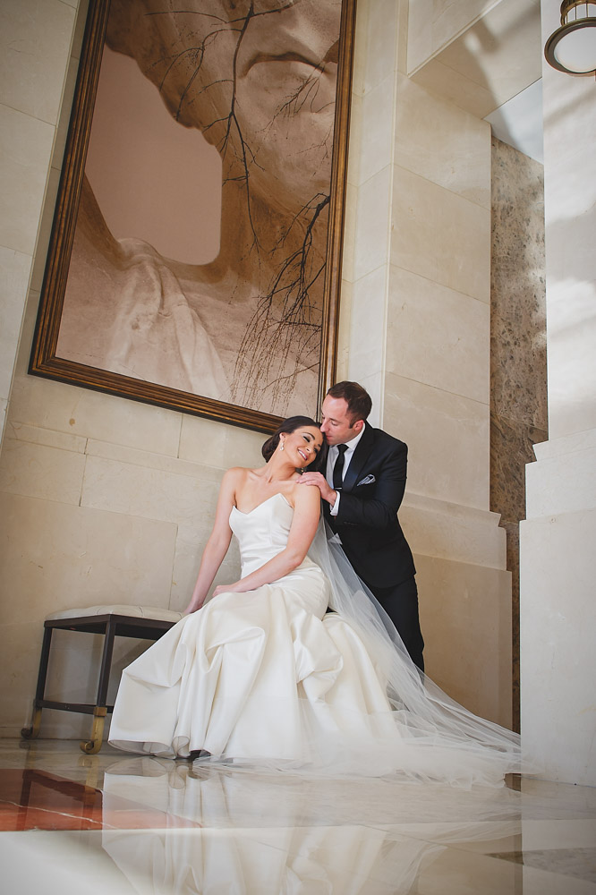 Bride in a ivory mermaid gown with groom resting beside her