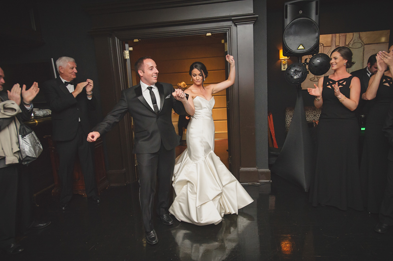 Bride in ivory mermaid gown and groom in black tux grand reception enterance_