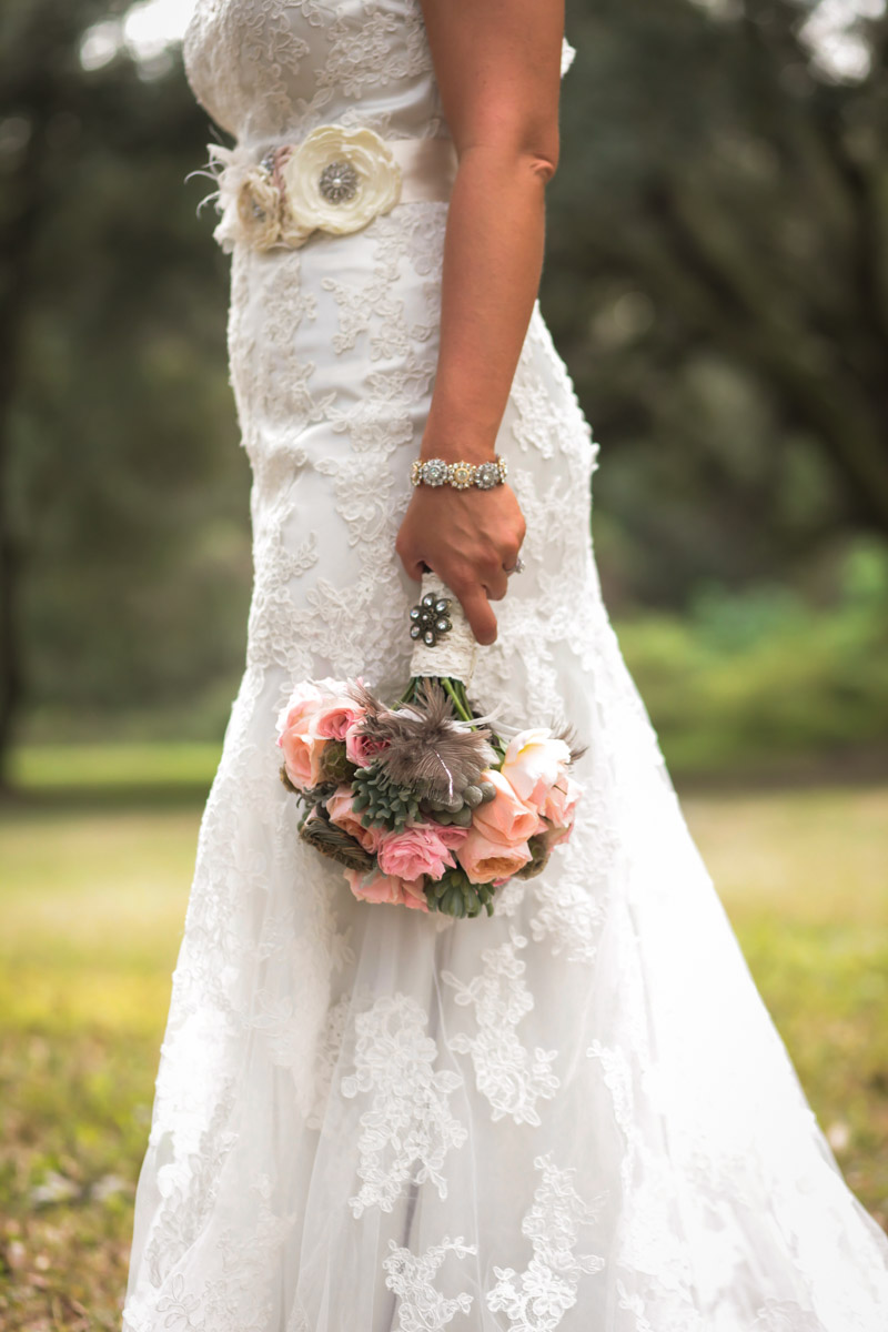 Bride in lace gown with blush rose, succulent, and feather bouquet_
