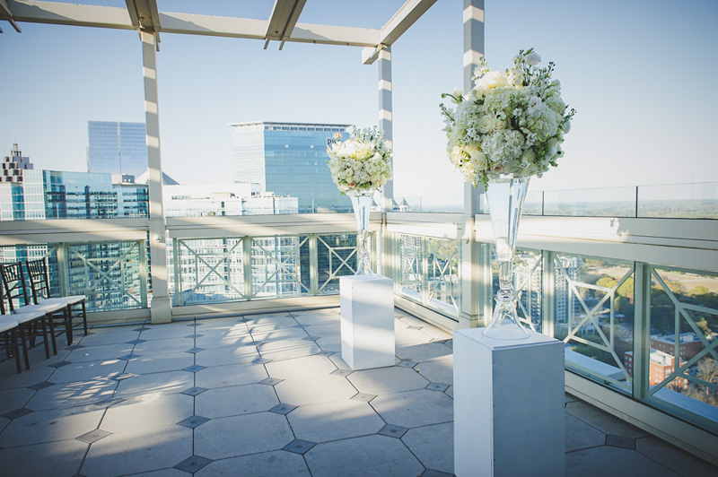 Ceremony rooftop shot with white hyrangea and rose vases