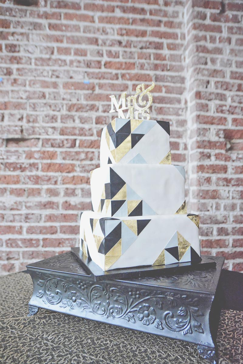 Close up of black, white, and gold three tier cake