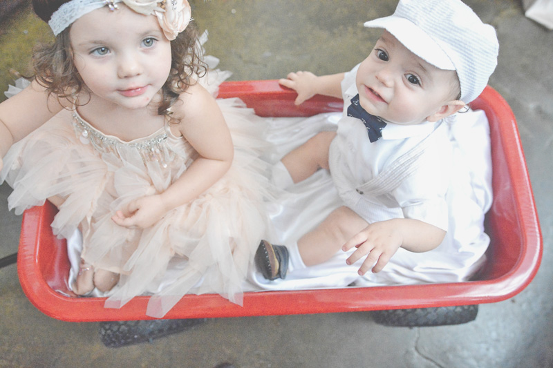 Flower girl and ring bearer sitting in a red wagon