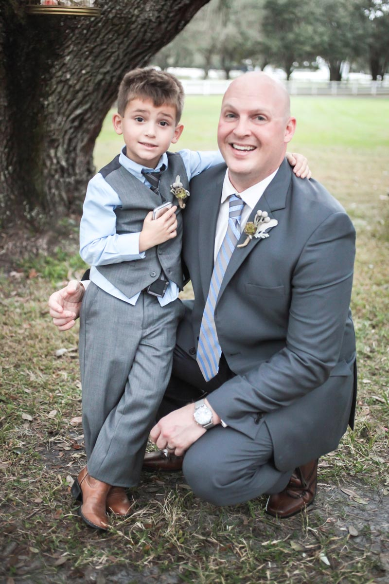 Groom in charcoal gray tux with ring bearer