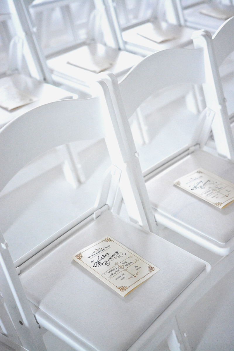 White ceremonial chairs with personalized ceremony program