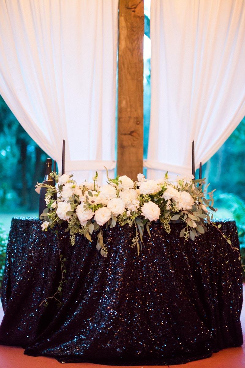 newyearsevewedding-headtable-whitefloral-blacksequintablecloth