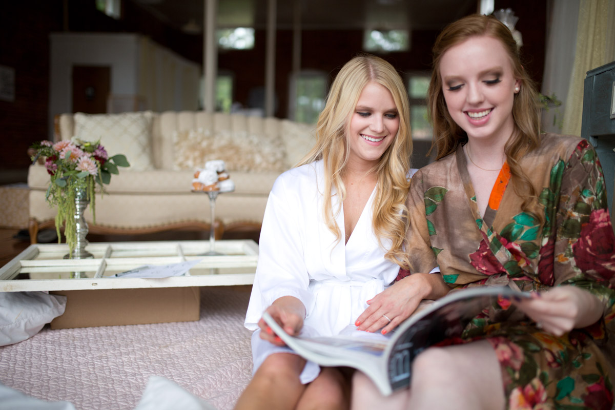 Bride and Bridemaid with Colorful Robes Looking At Magazine