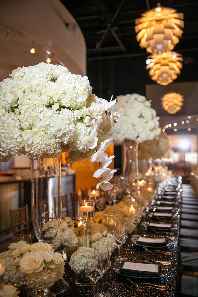 White Floral Centerpieces On Black Glitter Table Decor