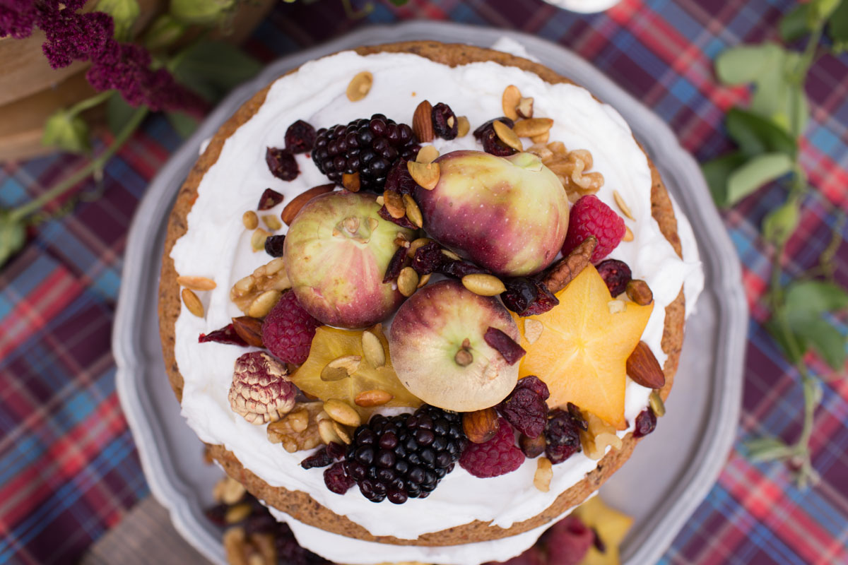 apples, nuts and berries on top of naked carrot cake